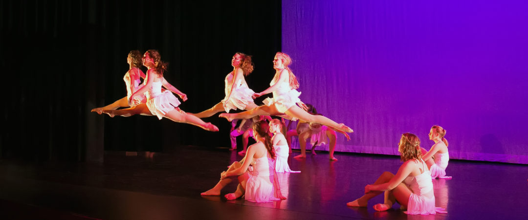 RMDT Spring Production dancers leaping on stage.